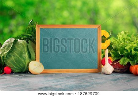 Chalkboard with set of different fresh vegetables on blue wooden table against background of green bokeh leaves