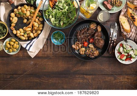 Dinner table with grilled steak grilled vegetables potatoes salad different snacks and homemade lemonade with border top view