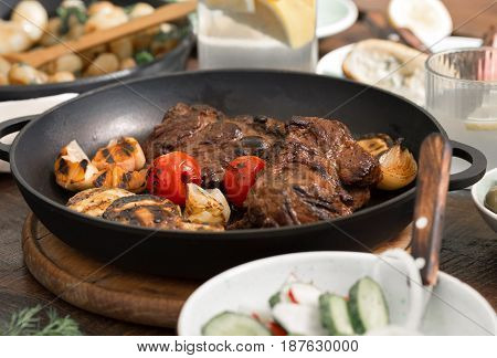 Beef steak grilled in a cast-iron grill pan on a wooden table close-up. Dinner table concept