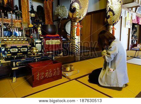 Kyoto, Japan - May 19, 2016. A woman praying at the ancient temple in Kyoto, Japan.