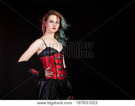 Sexy sensual woman in fetish red leather corset on black background in studio photo. BDSM and dominatrix