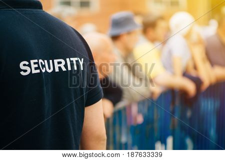 Member of security guard team working on public event unrecognizable male person from behind