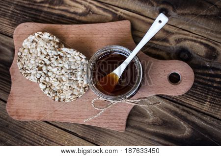 jar of honey with rice cookies on wooden background