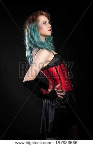 Attractive woman in fetish red leather corset on black background in studio photo. BDSM and dominatrix
