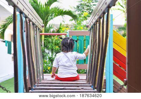 Asian little girl sit back on playground bangkok thailand