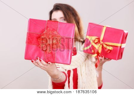 Young woman wearing red dress warm woolen shawl holding presents two gift boxes with ribbon. Christmas season celebration concept.