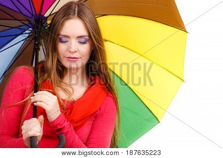 Woman fashionable rainy girl in red clothing standing under colorful umbrella. Meteorology forecasting and weather season concept