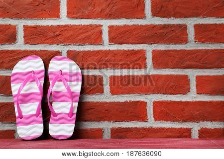 Pair of flip flops on a brick wall background