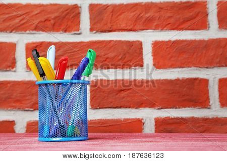 Colored pens in basket on brick wall background