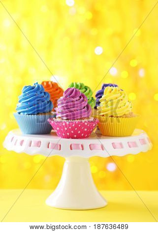 Tasty Cupcakes On A Yellow Lights Background