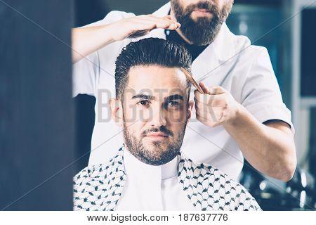 Horizontal indoors crop shot of man being combed in salon.