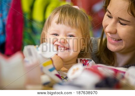 Mother and her little daughter have fun in children store, telephoto