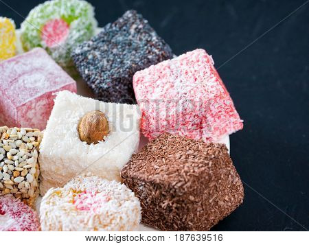 Turkish delight on black rustic background. Turkish deligh set. Assorted traditional turkish delight on oriental dark background