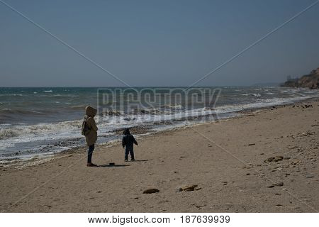 Sea landscape windy day beautiful waves and a young girl in a beige raincoat walking with a small son