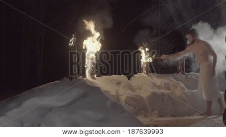 A man after sauna, in a towel barefoot on the snow setting fire to the log.