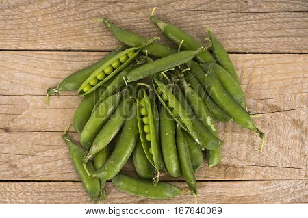 Green peas on a wooden background. Top view