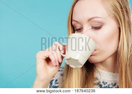 Morning drinks enjoying morning free time concept. Blonde woman drinking hot coffee or tea from white cup to feel warm