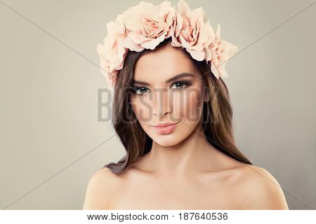 Female Beauty. Cute Woman with Perfect Makeup and Summer Rose Flowers on Gray Background