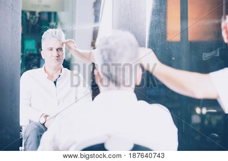 Stylish handsome man looking at mirror with confidence while hairdresser working with head.