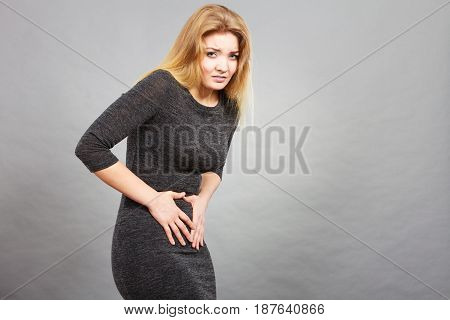 Woman having strong stomach ache. Syndroms of indigestion pregnancy. Female suffer on belly pain holds hands on abdomen on grey