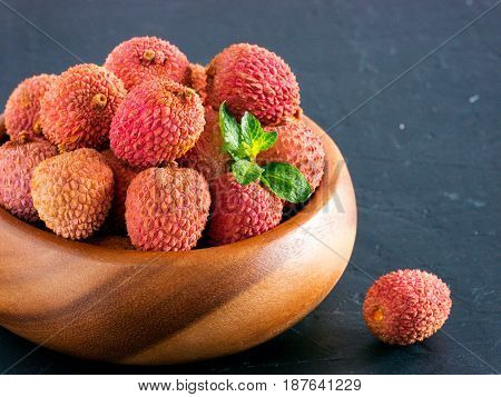 lychee fruit in clay plate on dark oriental background close up