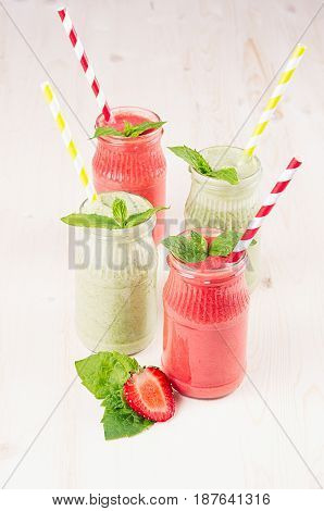Green and red fruit smoothie in glass jars with straw mint leaves strawberry and apples. White wooden board background copy space.