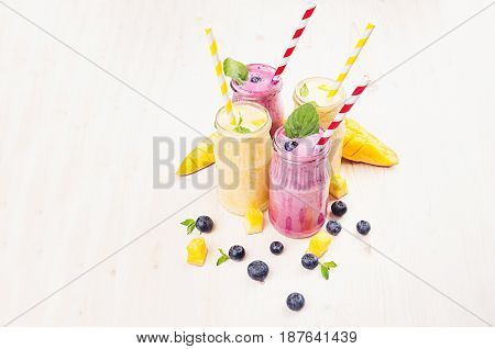 Freshly blended yellow and violet fruit smoothie in glass jars with straw mint leaves mango slices berry. Soft white wooden board background copy space.