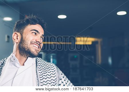 Horizontal indoors shot of cheerful man sitting and looking on side.