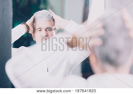 Horizontal indoors shot of man touching his stylish hairdo in barbershop.