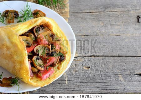 Mushrooms and tomatoes omelette. Homemade omelette stuffed with mushrooms, tomatoes and dill on a plate and vintage wooden background with copy space for text. Easy vegetarian breakfast. Rustic style