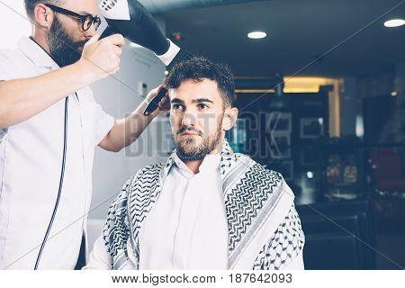 Horizontal indoors shot of man being dried in barbershop.