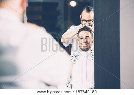 Barber making hair to man in salon. Horizontal indoors shot.