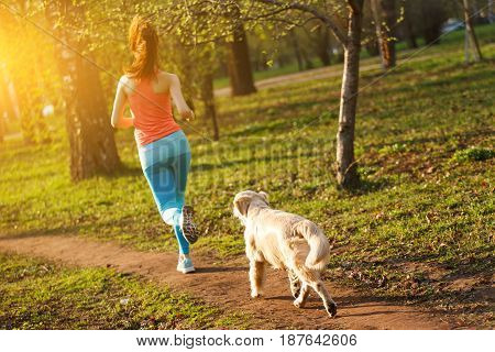 Woman with labrador run through park in afternoon
