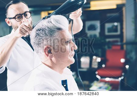 Side view of a stylistworking with drier and comb making a hairdo to mature man.