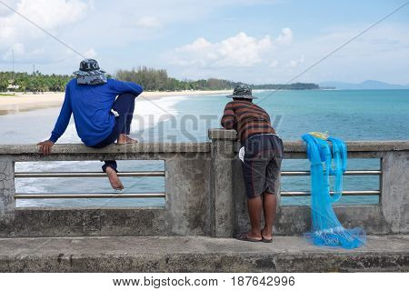 Fisherman Sitting On Concrete Bridge And Another One Fisherman Standing Beside Him. They Are Both Lo