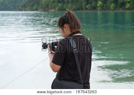 Asia Woman Wearing Black Shirt Standing On Beach And Using Camera For Take Photo. Have Blue Sea And