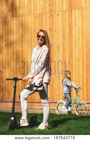 Woman with girl on bike ride near wooden fence during day