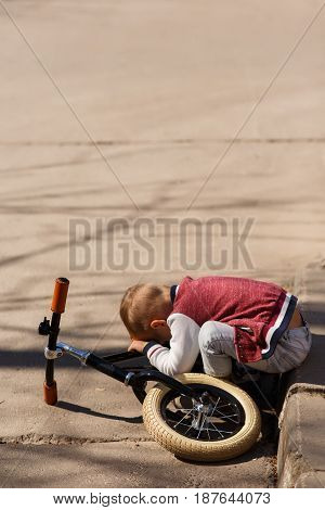 Photo of tired boy with bicycle in park