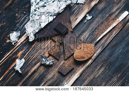 dark chocolate with Cocoa powder on brown wooden table. flat lay. top view.