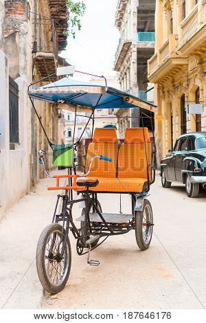 Cuban taxi bicycle parked in front of colorful colonial houses in havana