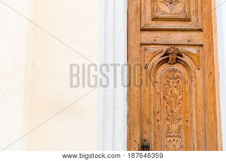 Old wooden door with paint and decrepit colored facade