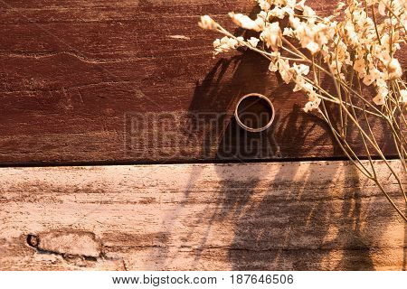 top view and warm tone. silver ring put beside white bouquet flower all of this putting on old wooden are background. this image for nature and flower concept