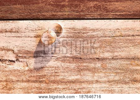 top view and warm tone. two silver ring putting on old wooden are background. this image for texture and accessory concept