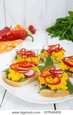 Sandwich with scrambled eggs rucola radish paprika kapi and flax seeds on a plate on a white wooden background.