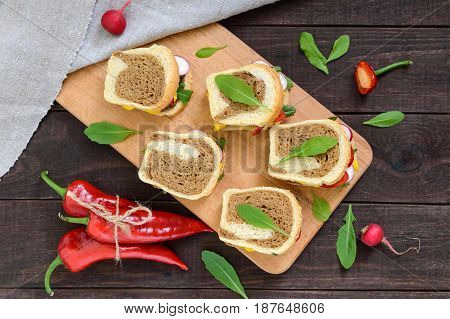 Sandwich with scrambled eggs rucola radish paprika kapi and flax seeds on a cutting board on a dark wooden background. Fast and tasty breakfast. The top view