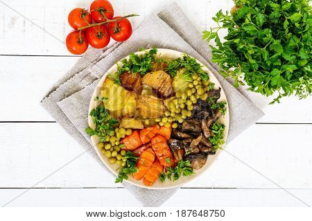 Vegetarian breakfast: baked vegetables (potatoes carrots) mushrooms green peas on a plate on a white wooden background. Healthy food. The top view