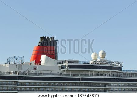 Upper decks and chimney stacks of a cruise liner during its stay over time in a harbor