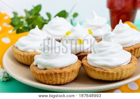 Mini tart with an air cream on a plate and a cup of coffee on a wooden background. Close up