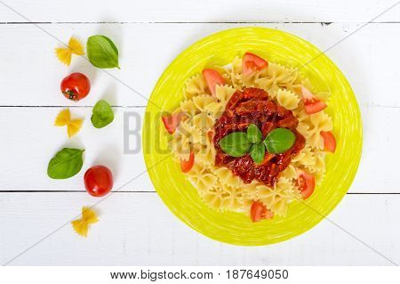 Pasta Farfalle with chicken tomato and tomato sauce on a plate on a white wooden background. A traditional Italian dish. Top view.