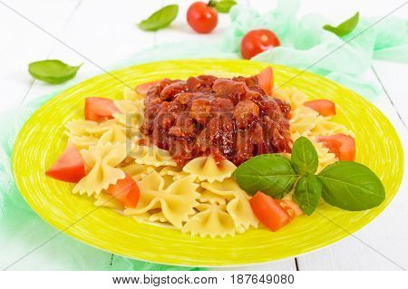 Pasta Farfalle with chicken tomato and tomato sauce on a plate on a white wooden background. A traditional Italian dish.